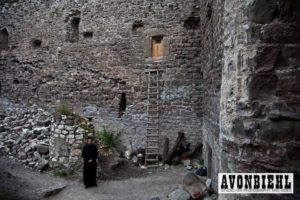 the inner courtyard of the mzovreti monastery where renovations and reconstruction continues a monk stands before a ladder to the rooms above
